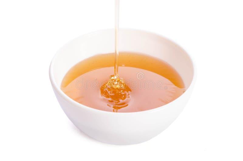 Лить мед в шар фарфора на белой предпосылке стоковые изображения