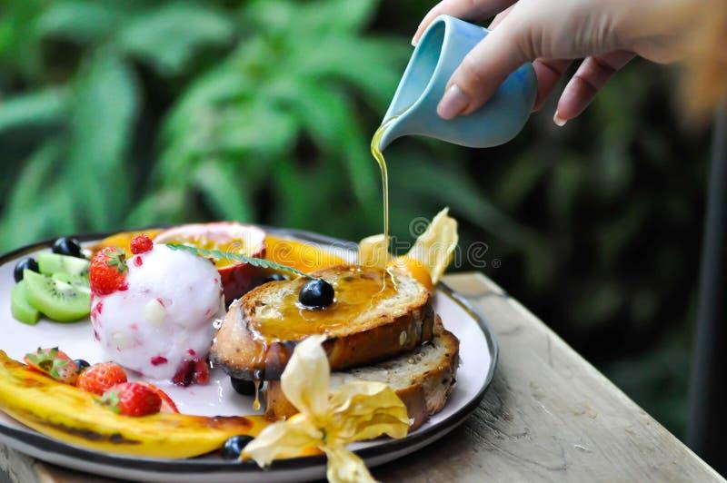Лить мед к мороженому ягоды с плодом и тостом стоковые изображения