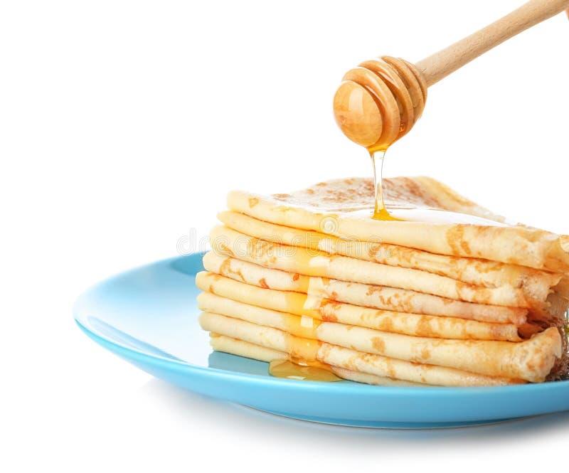 Лить мед на вкусные тонкие сложенные блинчики стоковые фото