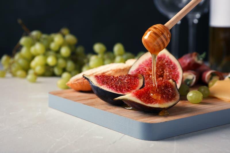 Лить мед на зрелые куски смоквы на деревянной доске стоковая фотография rf