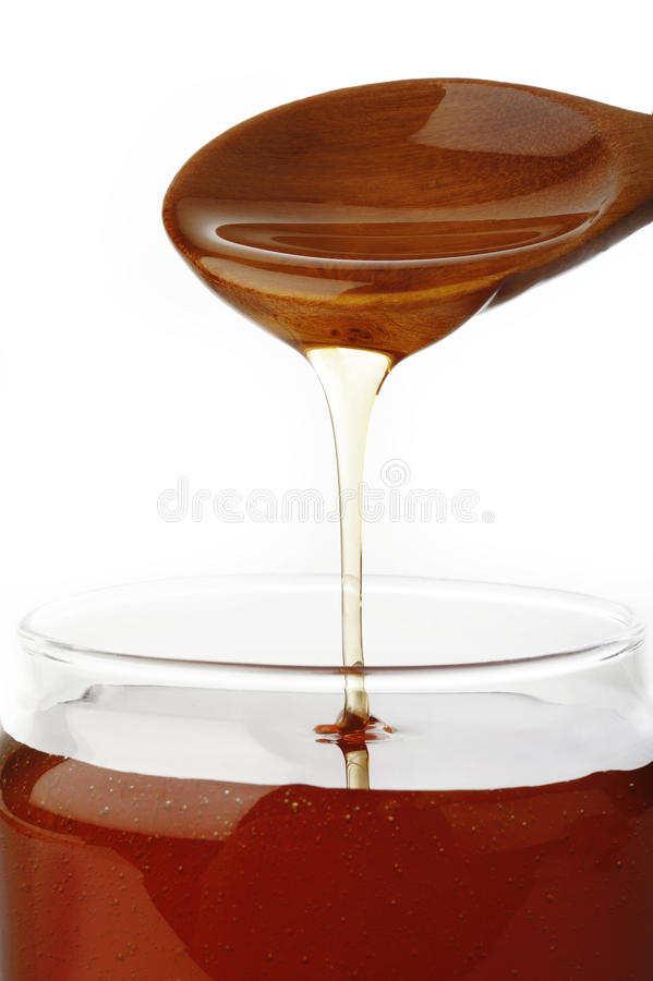 Лить мед от деревянной ложки стоковые фотографии rf