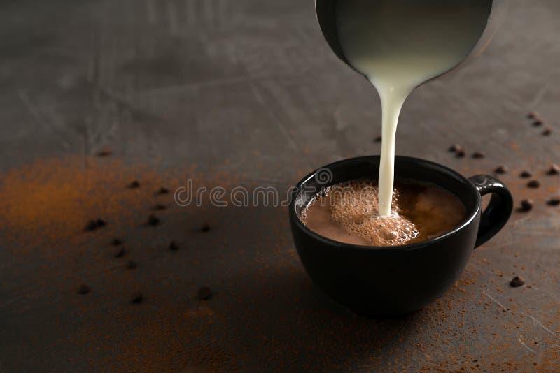 Лить молоко в чашку с вкусным горячим шоколадом на таблице стоковые изображения rf