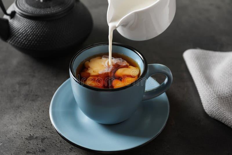 Лить молоко в чашку черного чая стоковые фотографии rf