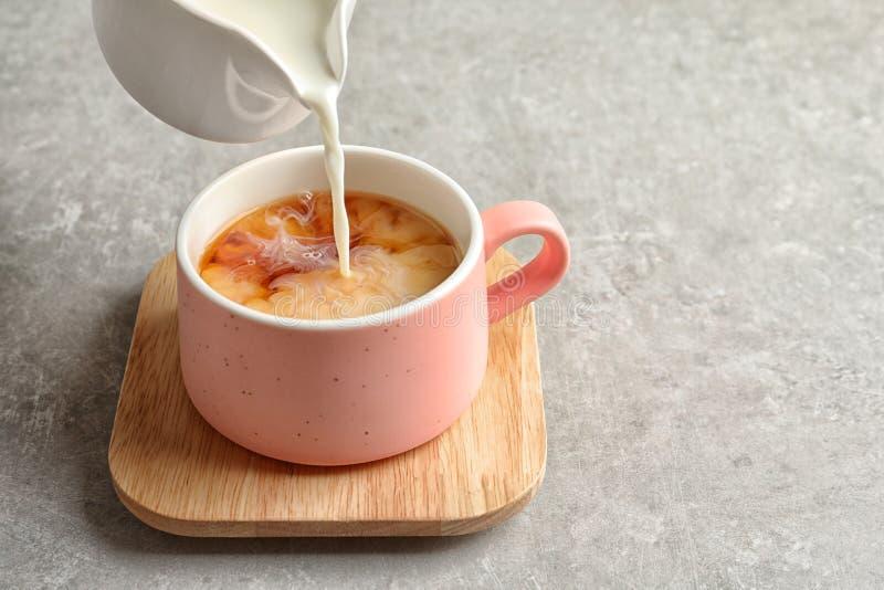 Лить молоко в чашку черного чая стоковые фото