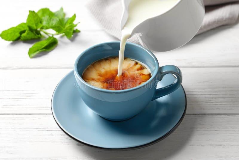 Лить молоко в чашку черного чая стоковое фото