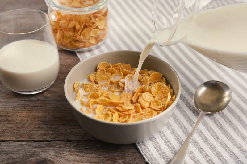 Лить молоко в шар с здоровыми корнфлексами стоковая фотография
