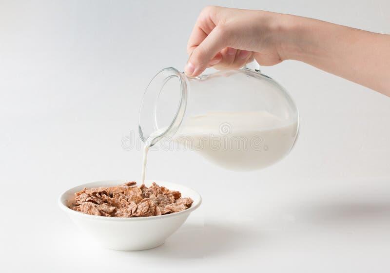 Лить молоко в шар с хлопьями multigrain естественными на белой предпосылке E стоковая фотография rf