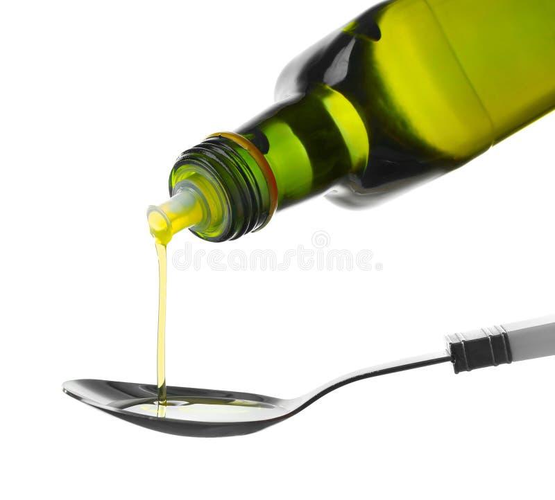 Лить оливковое масло от бутылки в ложку на белой предпосылке стоковая фотография
