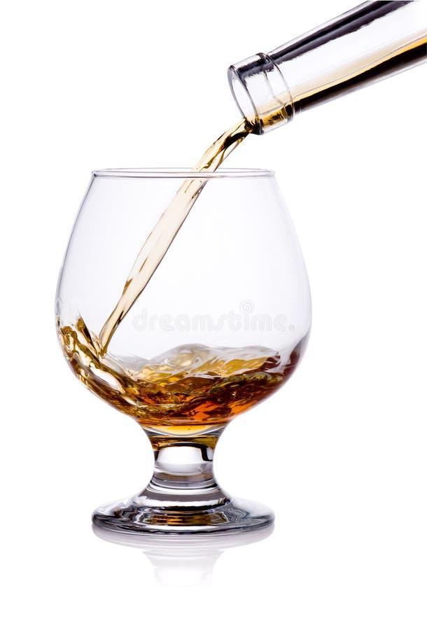 Лить от бутылки конгяка в изолированном стекле стоковое изображение