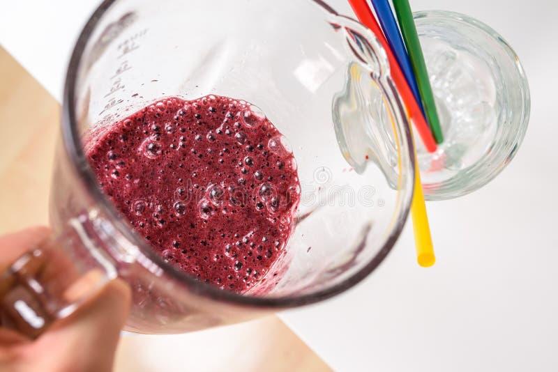 Лить очень вкусный сырцовый smoothie в стекло стоковое изображение rf
