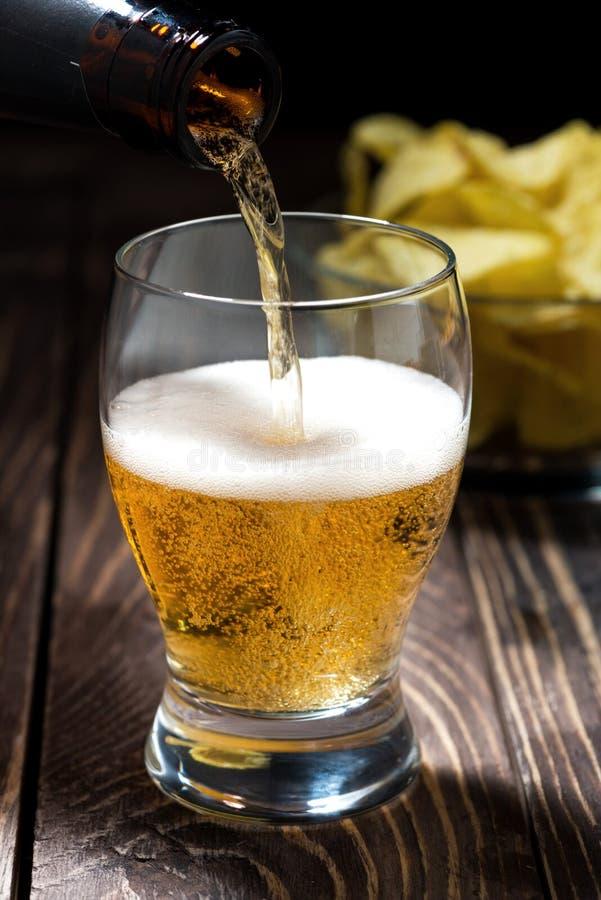 Лить пиво от бутылок и шара обломоков, вертикальных стоковое изображение rf