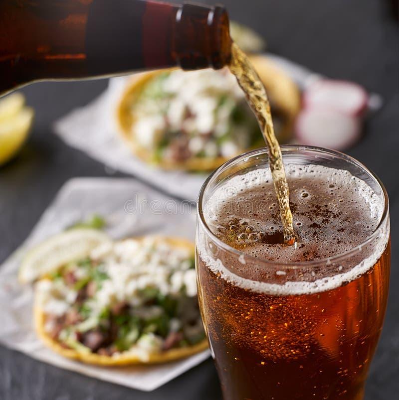 Лить пиво перед мексиканскими тако стоковое изображение rf