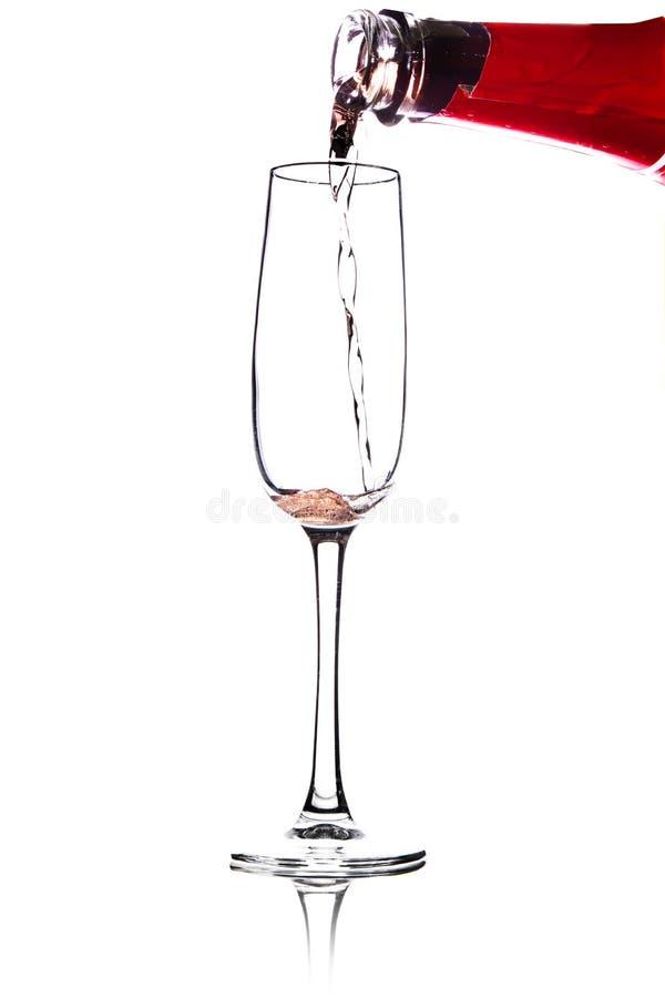Лить розовое вино в стекло, изолированное на белой предпосылке стоковая фотография