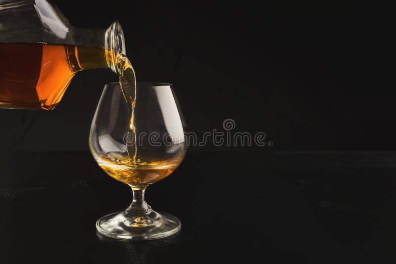 Лить рябиновка или коньяк от бутылки в стекло стоковые фото
