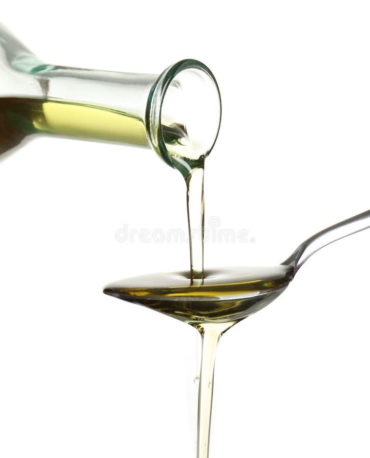 Лить свежее оливковое масло в ложку стоковые фото