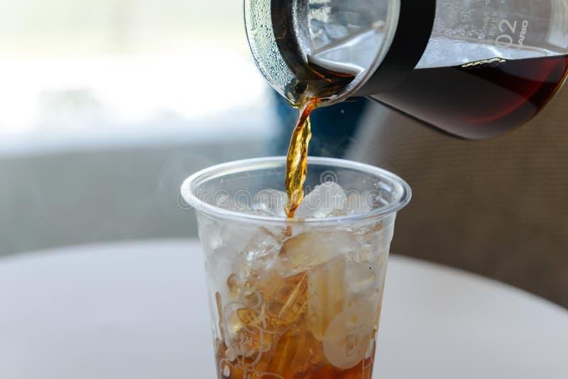Лить свежий заваренный кофе от бака кофе в пластиковое стекло льда стоковое изображение