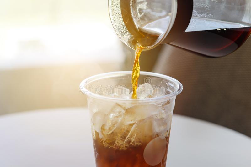 Лить свежий заваренный кофе от бака кофе в пластиковое стекло льда стоковая фотография