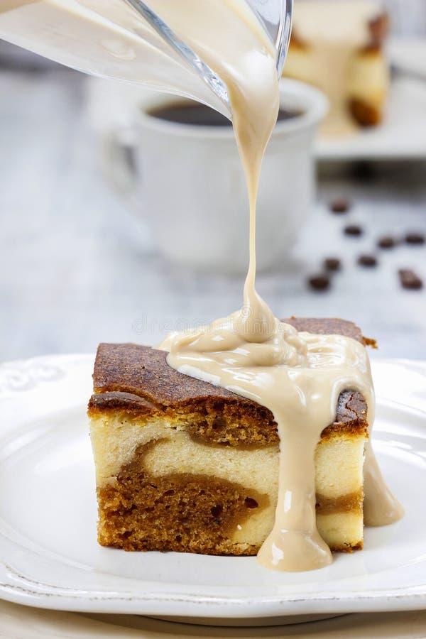 Лить соус карамельки на куске пирога стоковые фотографии rf
