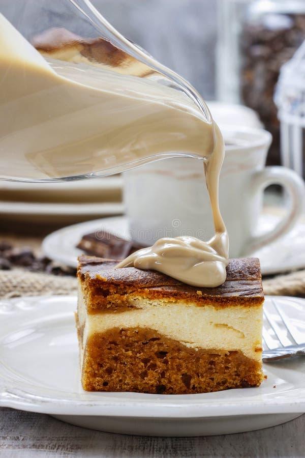 Лить соус карамельки на куске пирога стоковое изображение