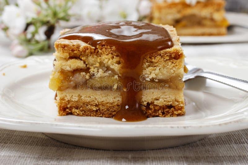 Лить соус карамельки на части яблочного пирога стоковое изображение
