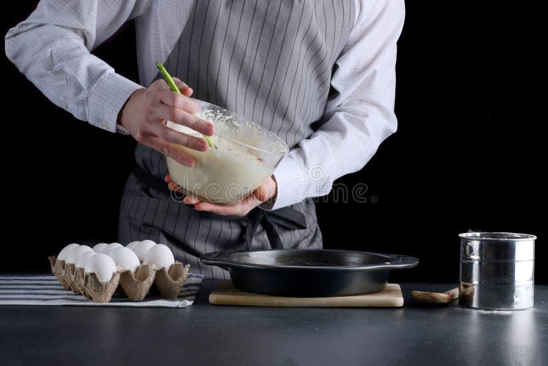 Лить тесто торта в олово выпечки шар владением человека и лить бэттер стоковое изображение rf