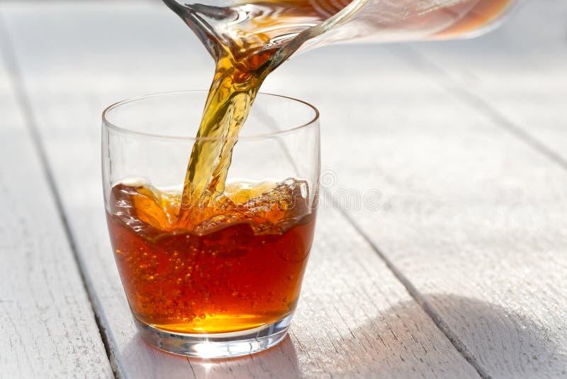 Лить чай льда от стеклянного кувшина в стекло Белое деревянное backgr стоковое фото rf