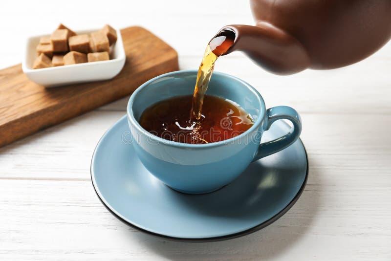 Лить черный чай в керамический cu стоковое фото