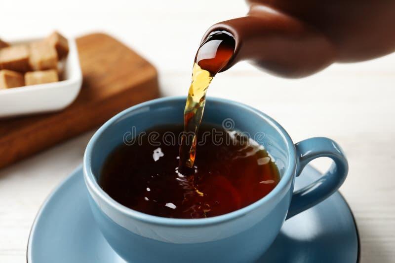 Лить черный чай в керамическую чашку на таблице стоковые изображения