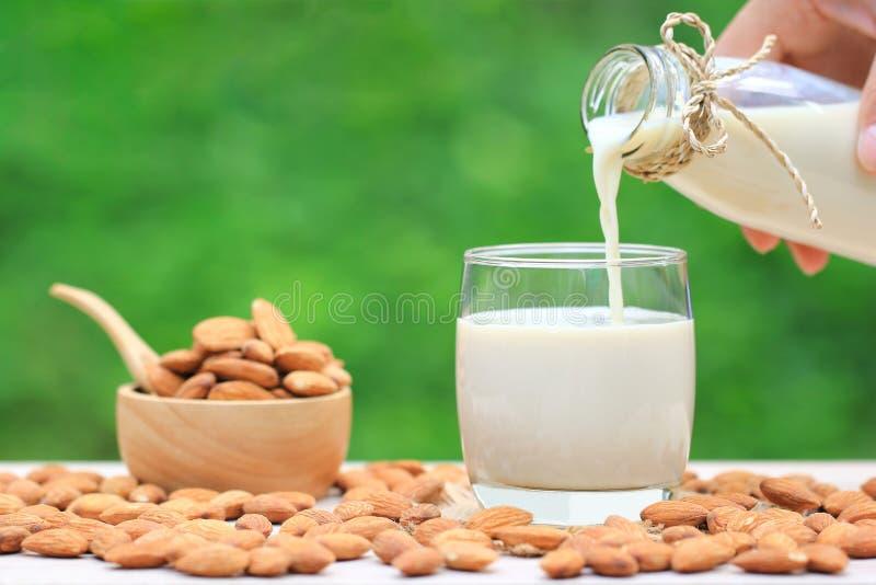 Лить чистое молоко миндалины от стеклянной бутылки с миндалинами в шаре на естественной зеленой предпосылке стоковые фото