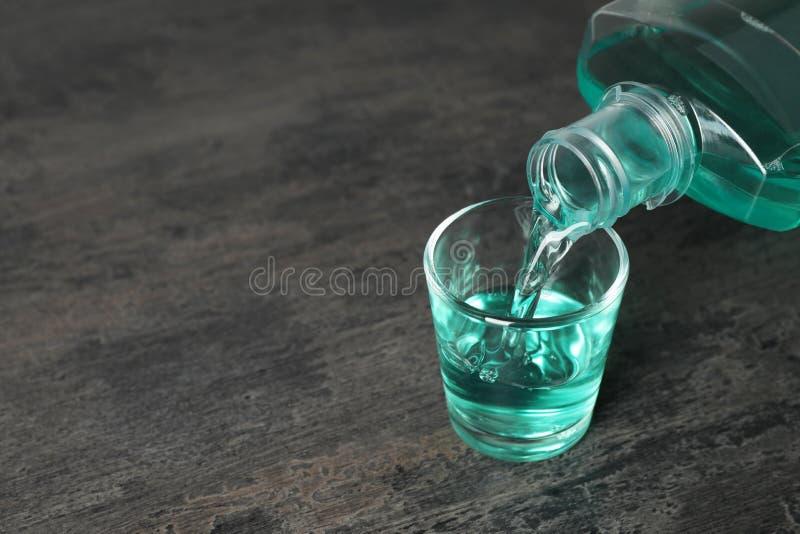 Лить mouthwash в стекле и космос для текста стоковое фото