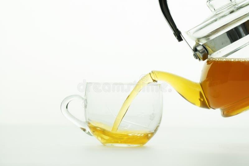Лить tae от чайника к стеклу чая стоковое изображение rf