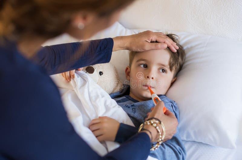 Лихорадка мальчика измеряя стоковое изображение