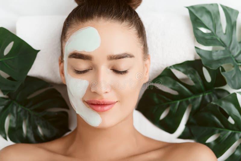 Лицевая маска Девушка лежа на таблице с тропическими листьями стоковые фото