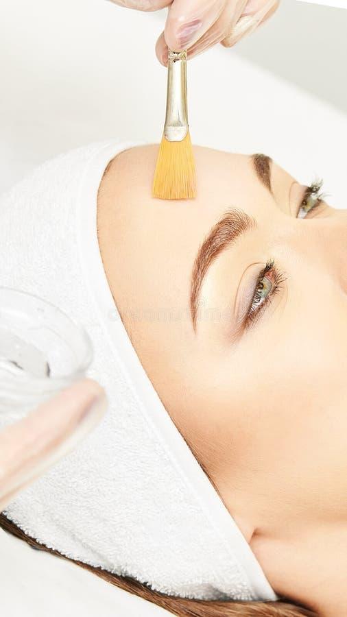 Лицевая обработка ретинола корки щетки Женщина красоты слезая процедуру Терапия маленькой девочки косметологии Hyaluronic кислота стоковая фотография