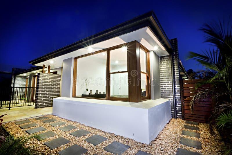 Лицевая сторона особняка загоренная на ноче с садом гравия стоковые фотографии rf