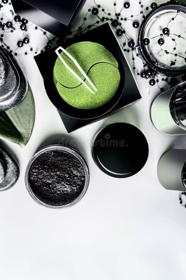 Лицевые косметические продукты устанавливая в черную и коричневую упаковку косметики естественные Современная забота кожи с запла стоковое изображение rf