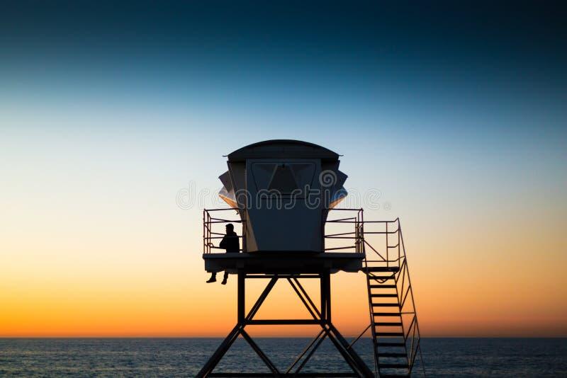 Личная охрана на пляже на сторожевой башне на заходе солнца стоковые изображения rf