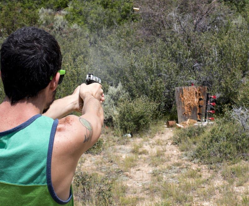 Личное огнестрельное оружие стрельбы человека на целях с раковиной в воздухе стоковая фотография rf