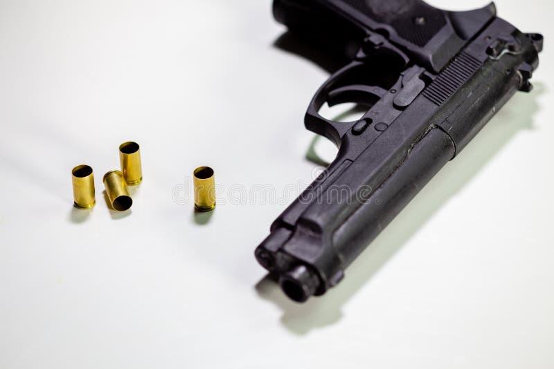 Личное огнестрельное оружие с кожухами раковины 9mm на белой таблице стоковые фотографии rf