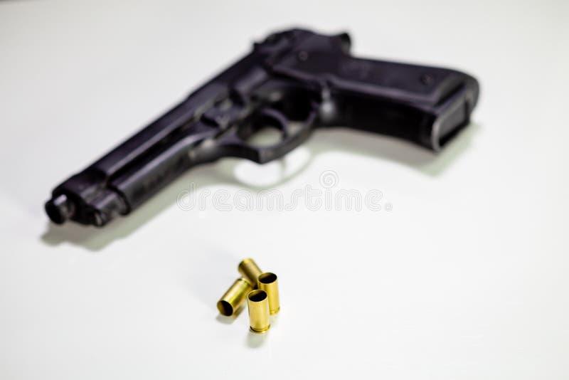Личное огнестрельное оружие с кожухами раковины 9mm на белой таблице стоковая фотография rf
