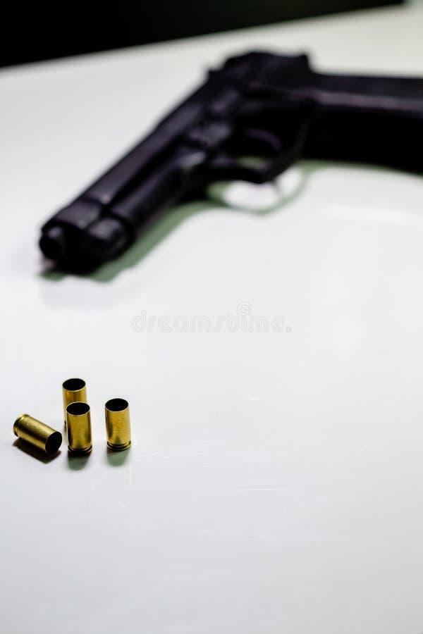 Личное огнестрельное оружие с кожухами раковины 9mm на белой таблице стоковое изображение