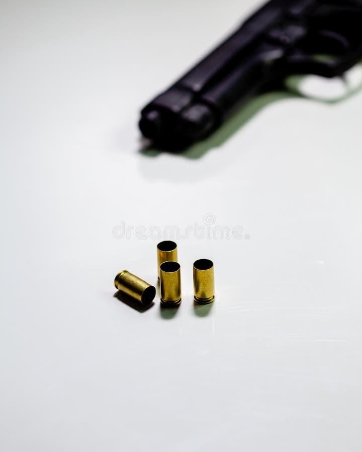 Личное огнестрельное оружие с кожухами раковины 9mm на белой таблице стоковое изображение rf