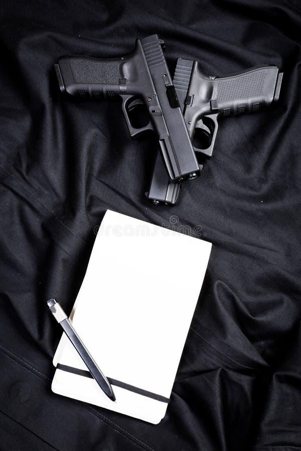 Личное огнестрельное оружие и тетрадь стоковая фотография rf