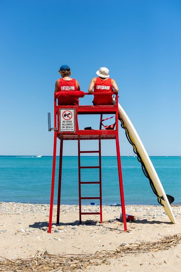 Личные охраны наблюдающ пляжем от башни стоковое фото