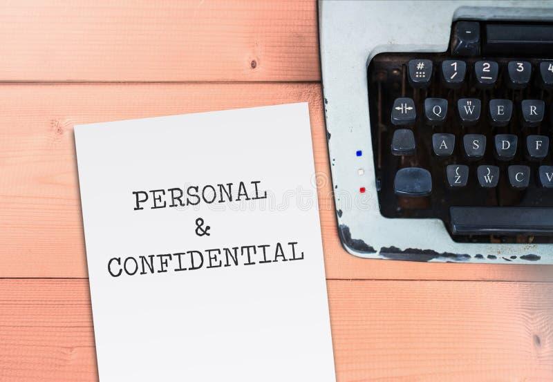 Личный и конфиденциальный на бумаге с машинкой на деревянной таблице стоковое изображение rf
