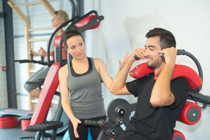 Личный тренер инструктируя тренирующую в спортзале стоковое изображение rf