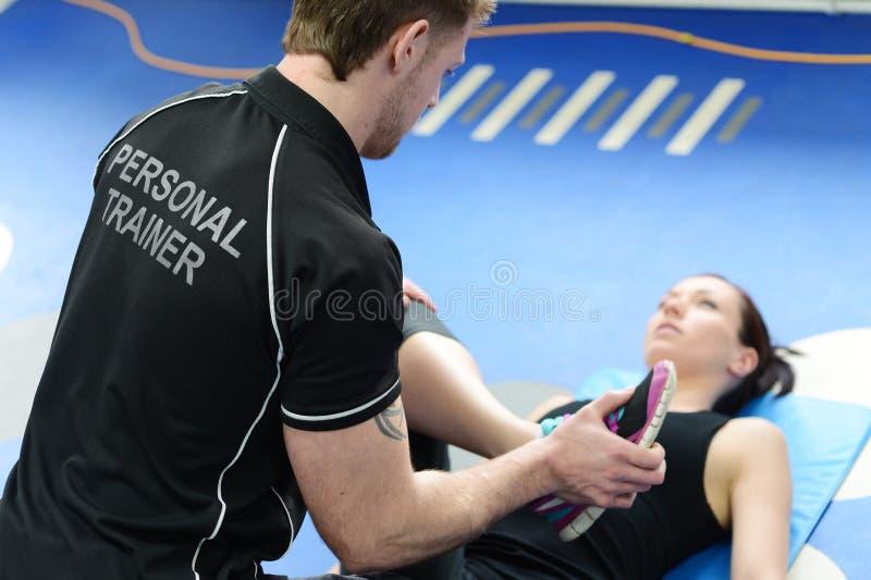 Личный тренер с протягивать девушки стоковое фото rf