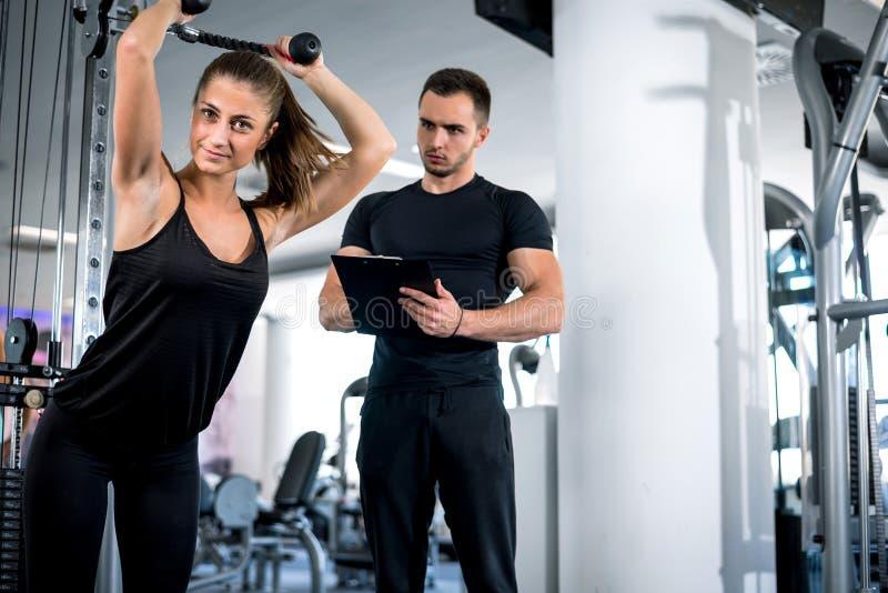 Личный тренер фитнеса с его клиентом в спортзале стоковые изображения rf