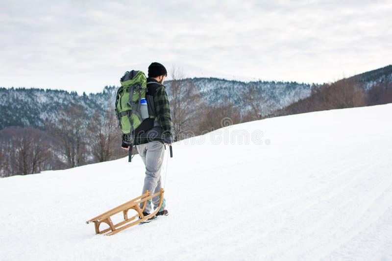 Ловкости человека puling поднимают снежную гору стоковое фото