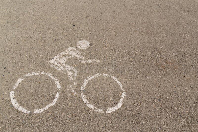 Логотип всадника велосипеда белый на том основании конкретный на дороге велосипеда стоковые фотографии rf